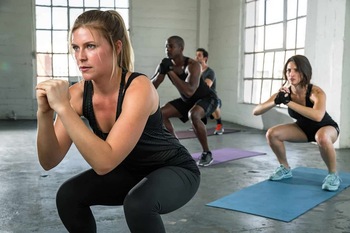 Boost your metabolism female instructor exercise squats unisex coed team