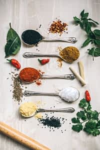 array of spoons filled with spices surrounded by herbs