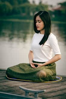 young woman doing relaxing deep breathing exercises on a dock