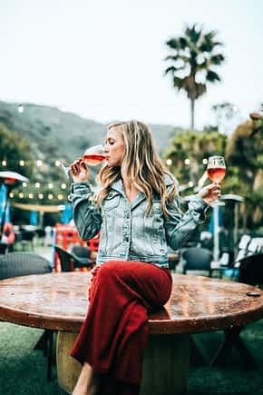 Young woman sipping from two glasses of rose wine