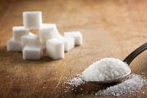 white granulated sugar and sugar cubes on a table