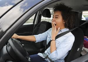 fatigued woman behind the wheel of a car