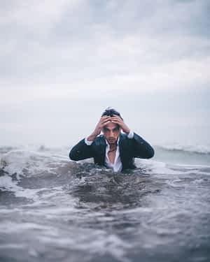 Man in suit emerging from ocean water