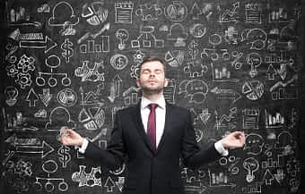 Businessman meditating in front of chalkboard with complex illustrations