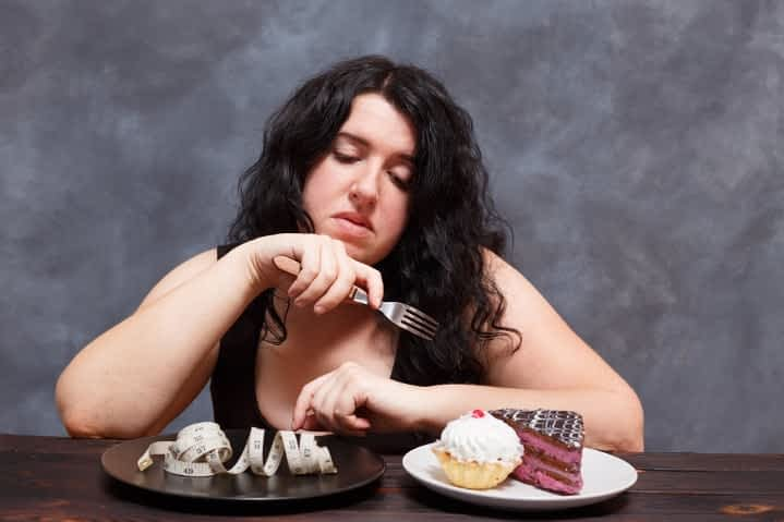Overweight woman struggling with choice of snack foods over weight loss