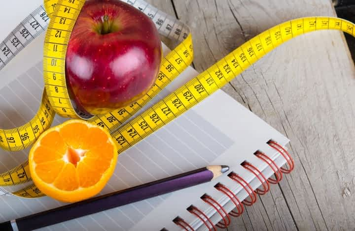 measuring tape, planner, and ready to eat fruit