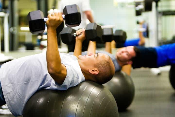 men lifting weights on balance balls in gym