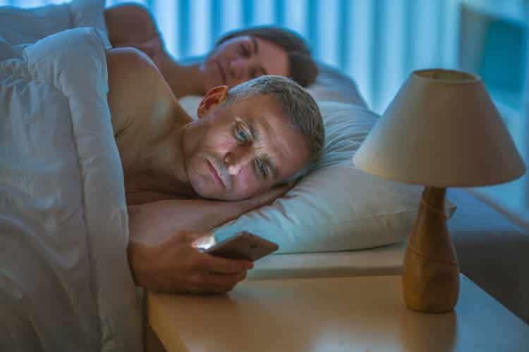 sleepless man looking at phone with partner asleep next to him