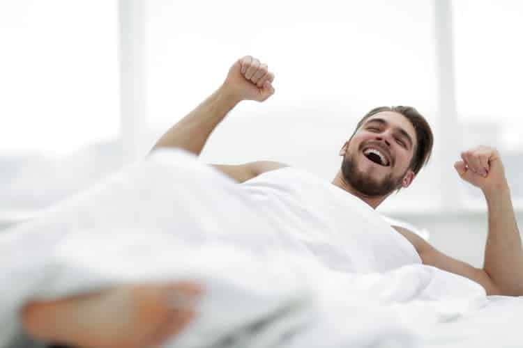 bearded man waking up with a smile on his face after good night's sleep