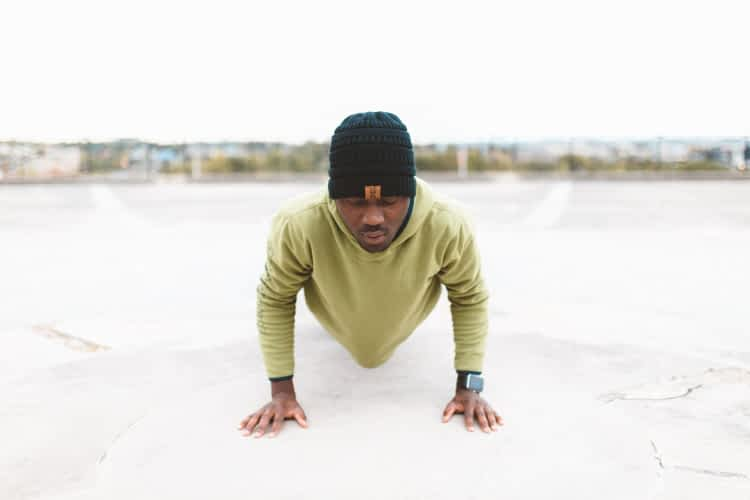 Fit man doing pushups on ball court