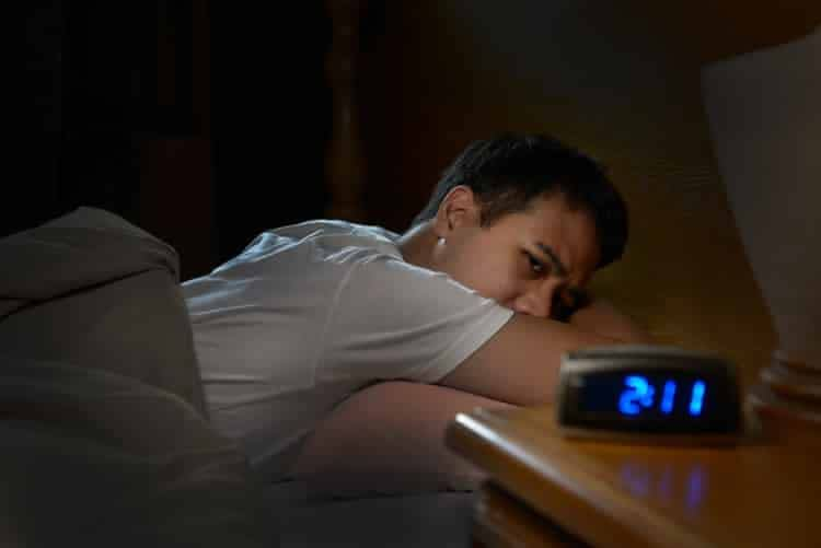 man with insomnia staring at alarm clock in the early morning